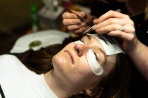 Person receiving eyelash extensions.
