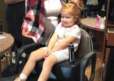 Child in wedding party getting hair styled.